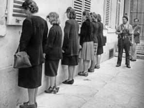 """Donne accusate di """"collaborazione orizzontale""""con i nazisti sono allineate contro il muro dai partigiani durante la liberazione di Chartres. Credits: Rue des Archives /RDA /Tips Images"""