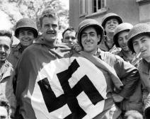 Cherbourg, Soldati americani mostrano vittoriosi una bandiera nazista. (1 luglio 1944) Credits: Rue des Archives /RDA /Tips Images