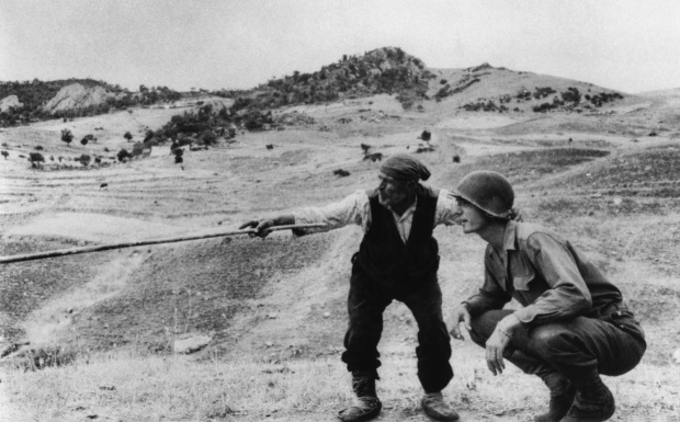 Photography by Robert Capa©International Center of Photography/Magnum - Collection of the Hungarian National Museum:Agricoltore siciliano mostra ad un soldato americano in quale direzione sono andati i tedeschi, vicino a Tirano, 4 - 5 agosto 1943.